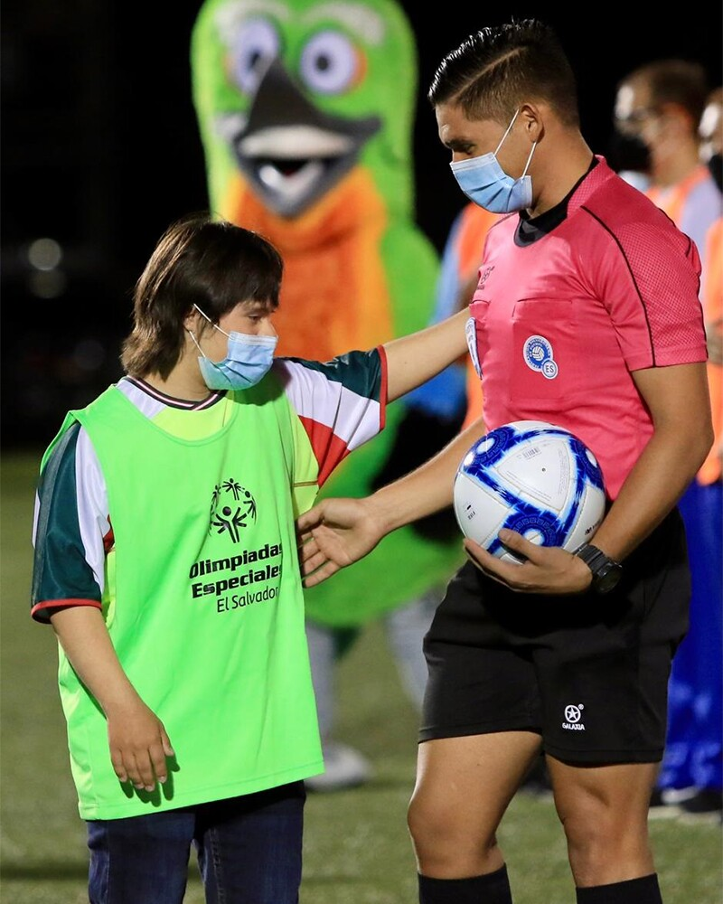 Special Olympics El Salvador athlete escorting referee onto the playing field.