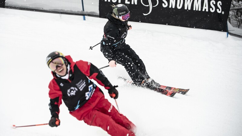 Two skiers are racing down the hill looking very happy. The one skier at the front of the photo is in red, and the one at the back is in black.