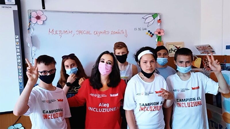 An adult woman stands with her arms around a group of approximately six students inside a classroom. Everyone wears facemasks, and some students hold up peace signs.