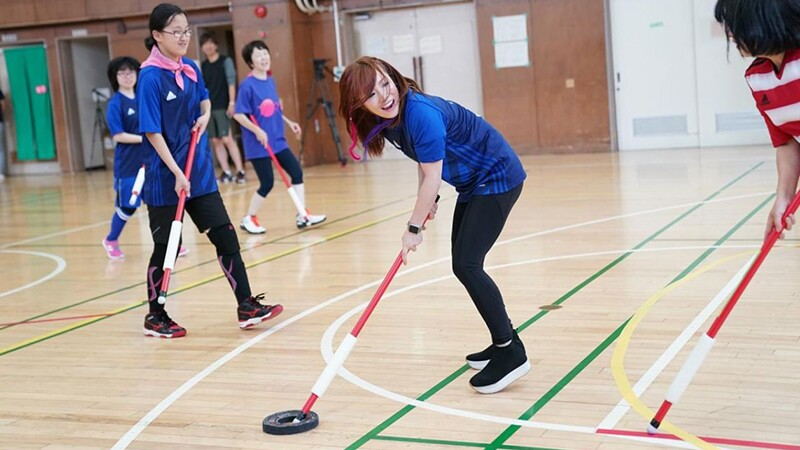 Young woman with red and blue hair plays a unified game of floor hockey with athletes and other unified partners.