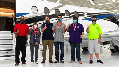 Six individuals (3 with metals around their necks) standing in front of an aircraft.