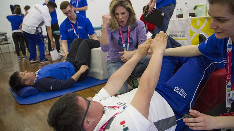 An athlete performing crunches while volunteer and Julian Micheles cheers him on.