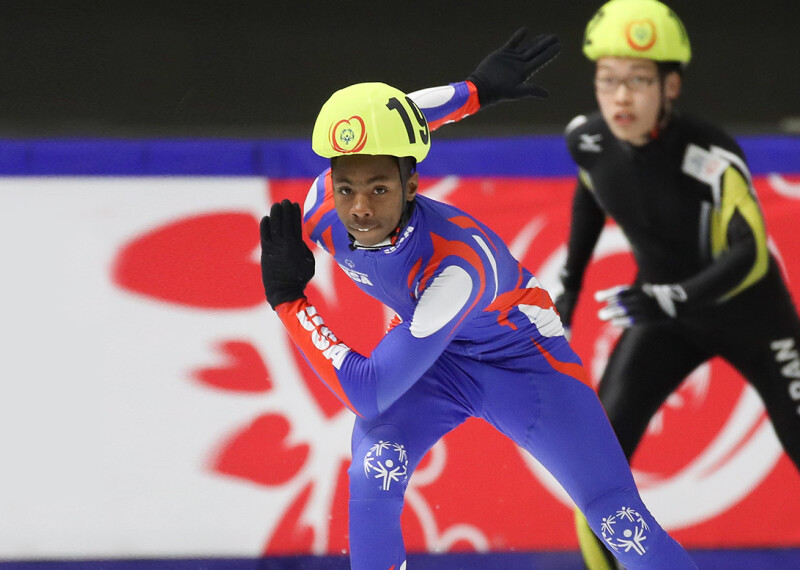 A Special Olympics USA speed skater races during the 2017 Special Olympics World Games in Austria as a competitor from Japan looks on.