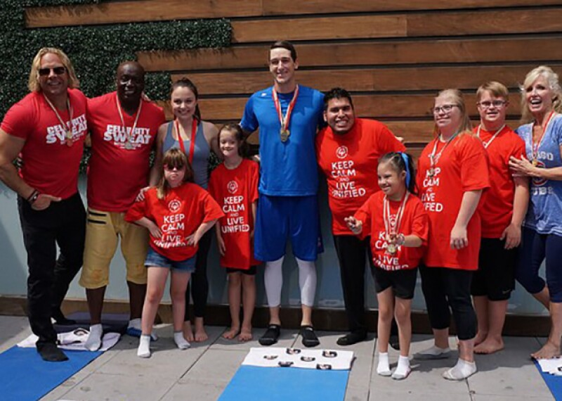 Chicago Cubs Pitcher, Kyle Hendricks, stands with athletes and two Celebrity Sweat celebrities after participating in Yoga. Athletes are in shorts and a red shirt that reads Keep Calm and Live Unified and some of the athletes have medals around their necks. Kyle in all blue and white tights has a medal around his neck.