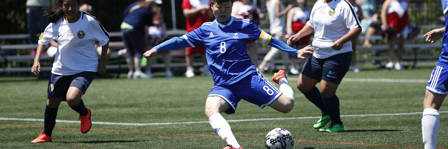 Female player draws her leg back to kick the ball as players on the opposing team watch.