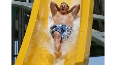 Young man sliding down a water slide.