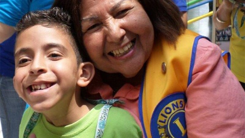 A woman in a yellow Lions Clubs vest hugging a young boy and both are smiling.
