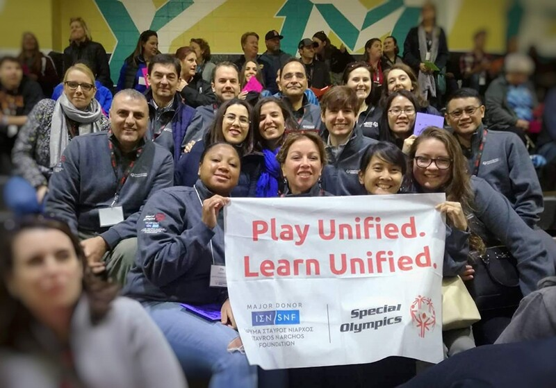 Special Olympics staff and representatives at a Play unified Learn Unified event sitting in a group holding up a banner.