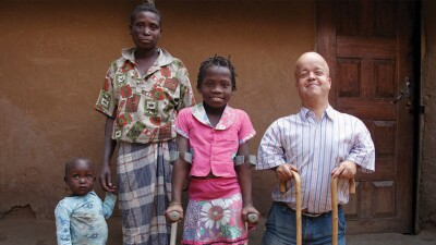 A young boy on the left hold a mother figures hand; a young girl with crutches dressed in floral and pink in the center; a young man with two canes standing and smiling.