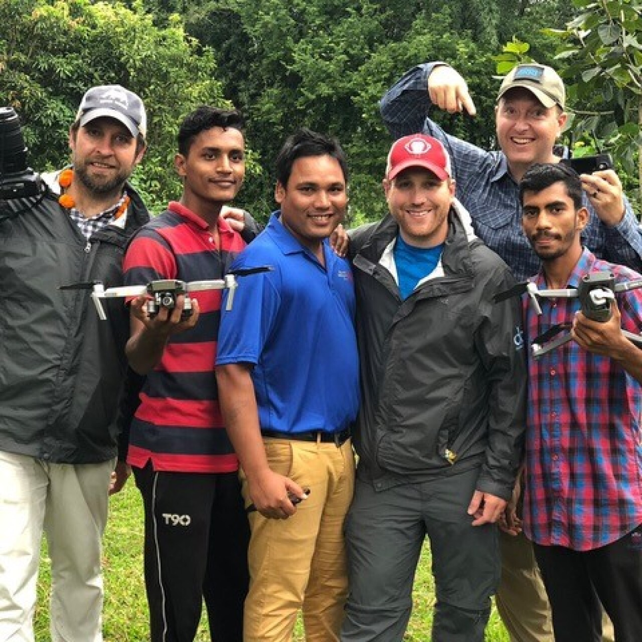 The camera crew and local men are outside in front of trees and brush standing for a group photo; there are six men total. A man on either side are holding drones.
