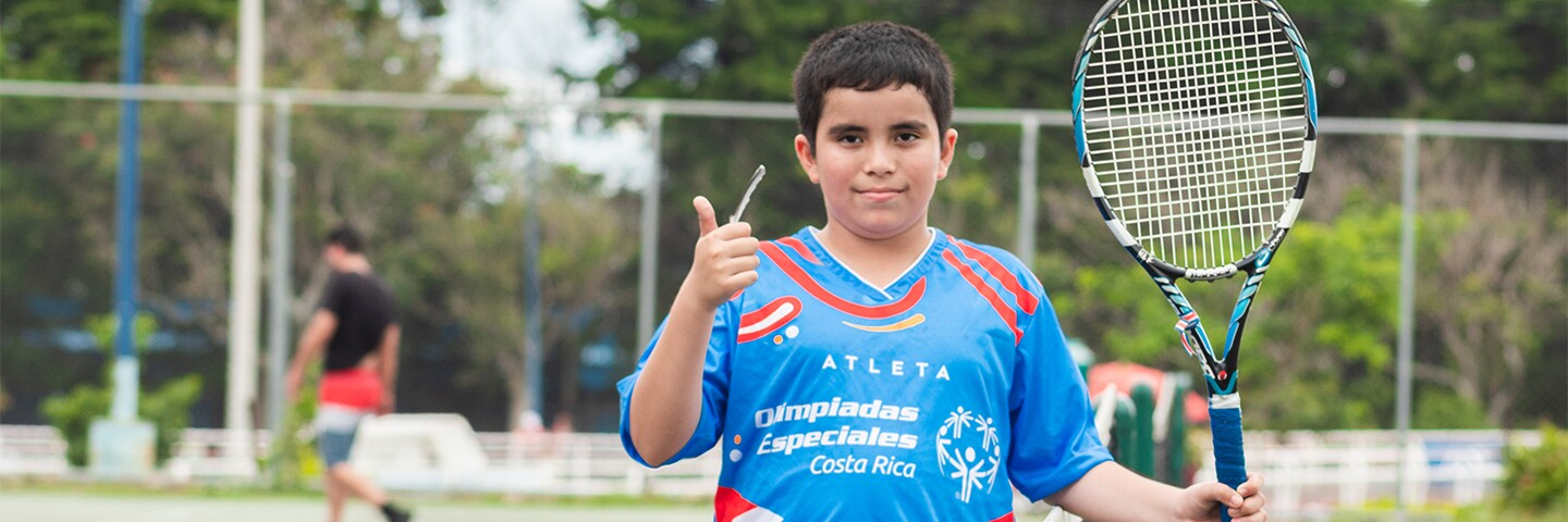 AJ (from Costa Rica) on the tennis court giving a thumbs up and holding a tennis racket.