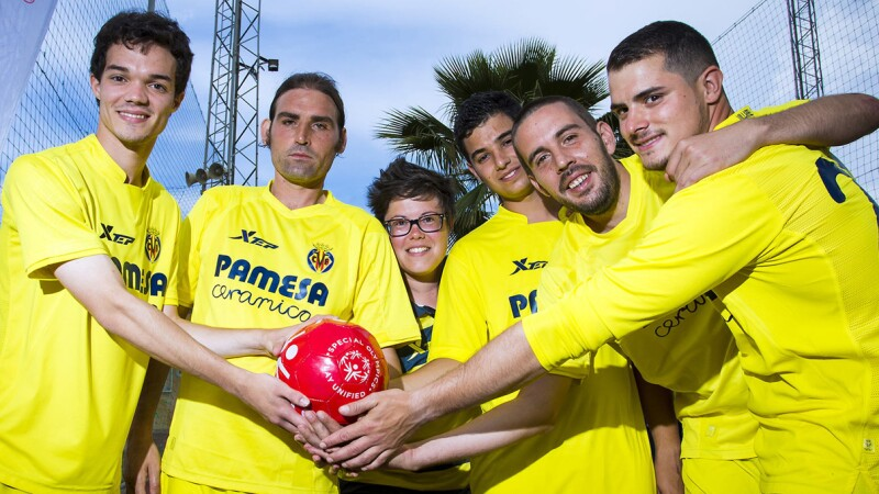 Unified footballer group of 6 people, one female and five male, all wearing yellow shirts and shorts with their hands together holding a red Special Olympics Play Unified football.