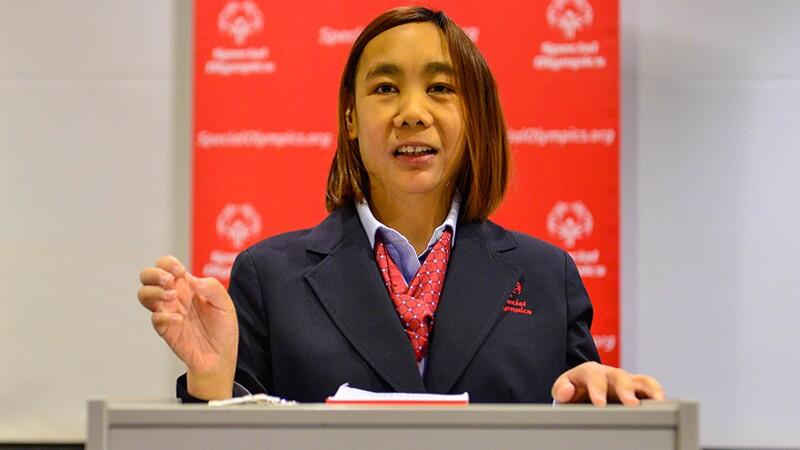 Woman standing behind a podium giving a speech.