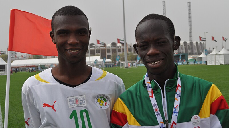 Aboubakrine Sadikh Diaw and Mame Ndiagne Ndiaye standing side by side on the football field. Mame has his hearing aids in.