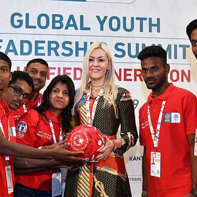 Athletes and SO representative standing together holding a signed football (soccer ball).