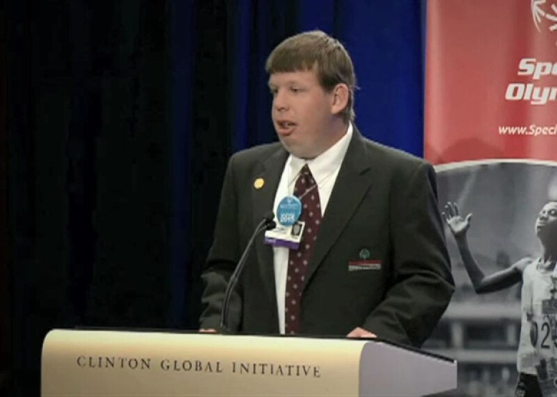 Dustin speaking on stage at a podium that reads: Clinton Global Initiative.