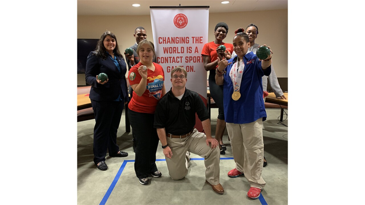 Group of seven athletes standing in front of a sign that reads, Changing the world is a contact sport, game on. Some of the athletes are holding Bocce balls.