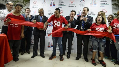Athletes and representatives cut a ribbon in front of a Healthy Athletes backdrop.