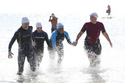 A man and three women wearing wet suits and swim hats and goggles on their heads, hold hands and smile as they walk out of the sea together with water splashing around their legs.