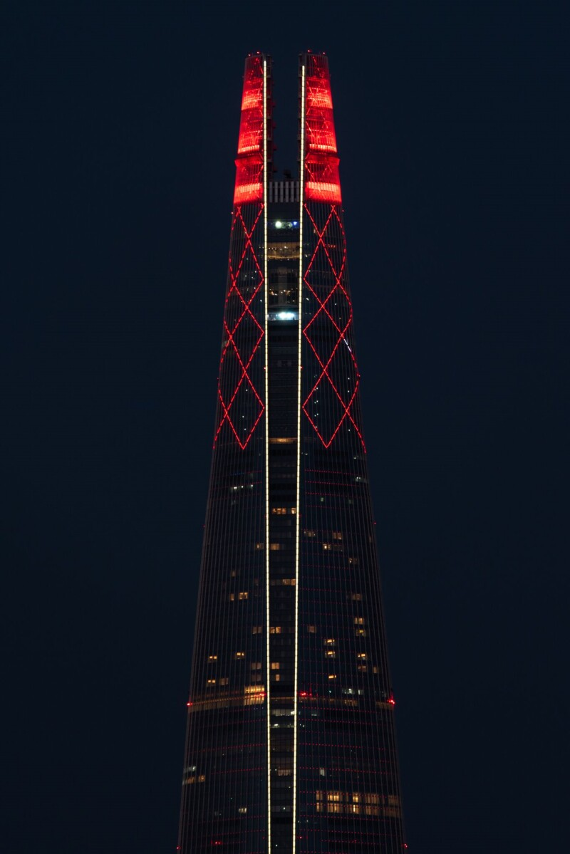 Jamsil Lotte World Tower, the tallest building in Korea, lit up red at the top, the night dark night sky is in the background.