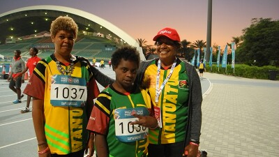 Two athletes and a coach stand in front of the stadium in Abu Dhabi.