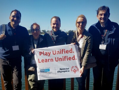 A group of five people stand holding a white banner that reads 'Play Unified. Learn Unified.' with the sea and blue sky in the background.