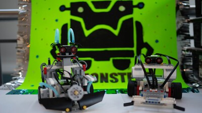Two robots in front of a robot monster logo.