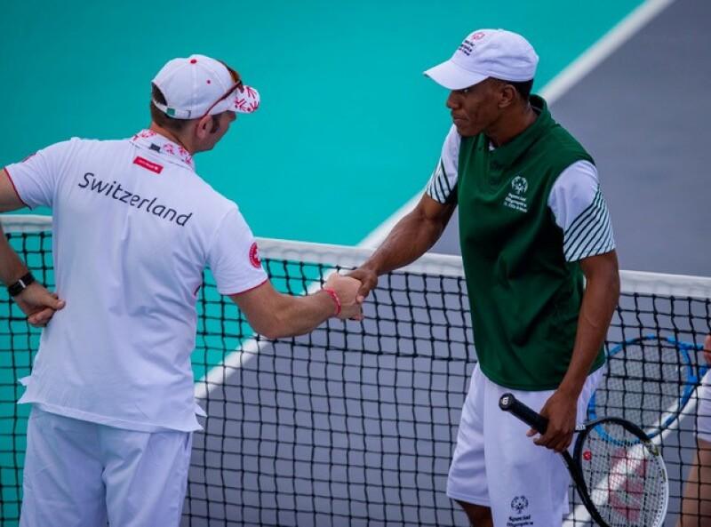 Two Special Olympics athletes shake hands at the end of a tennis match.