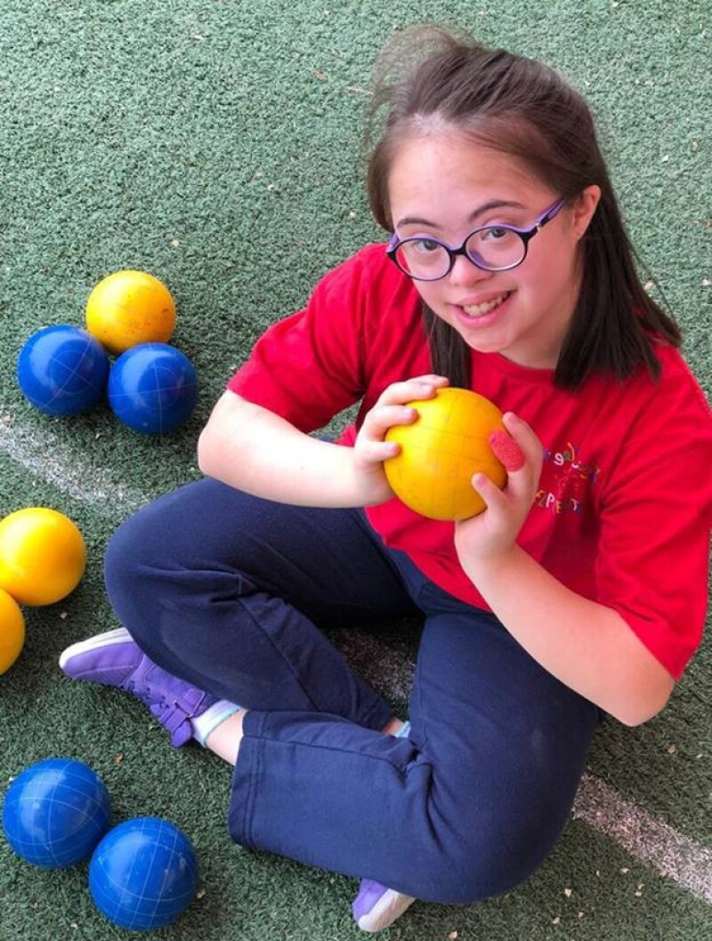 Sara Felemban sitting on a Bocce court holding a bocce ball looking up at the camera and smiling.