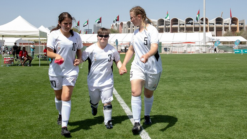 Three female footballers walking on the field hand in hand wearing all white.