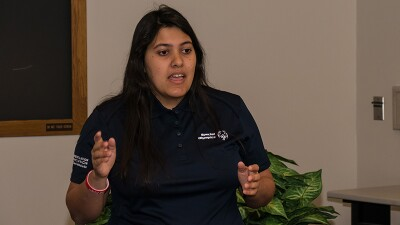 Emanuelle de Souza speaking to an interviewers. She is in a black Special Olympics polo that reads, The Revolution is Inclusion on the sleeve.