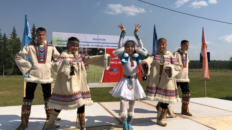 Five young people in traditional costumes pose on a stage with grass and a blue sky in the background.