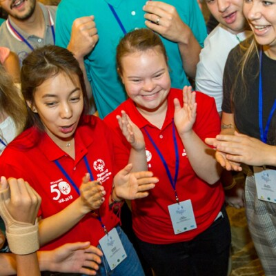 A large group of athletes and Special Olympics representatives stand in a circle clapping with joyful expressions on their faces.