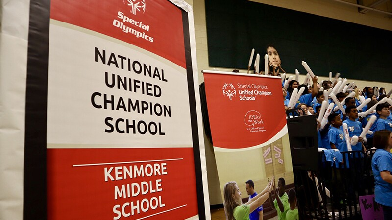 Signage for Special Olympics National unified Champion School Kenmore Middle School. Spectators are in the background.