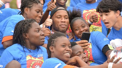 Didier Drogba surrounded by athletes for a group photo.