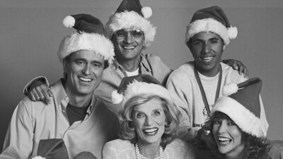 A Very Special Christmas sponsors and singers in a group wearing Santa hats.