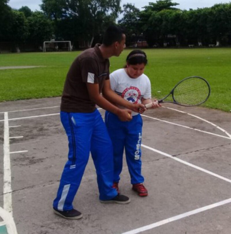 Instructor is teaching a young girl on the court; the instructor is teaching the young girl how to hold a tennis racket.