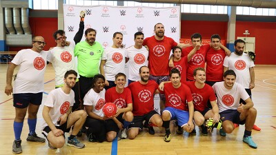Full group including WWE star, athletes, and volunteers on the court posing for a group photo in front of a WWE and Special Olympics backdrop.
