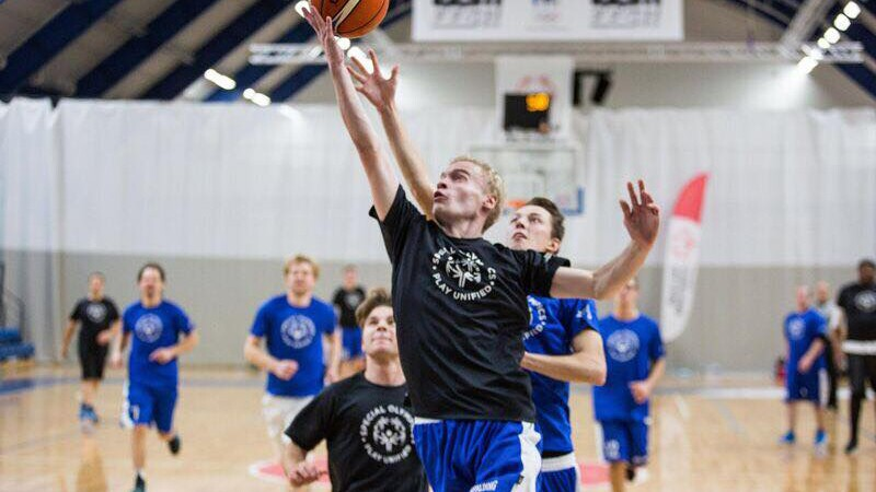 One player in a black play unified t-shirt jumps for a layup shot; a player in a blue play unified t-shirt attempts to block the shot; players behind watch the action and run toward the action.
