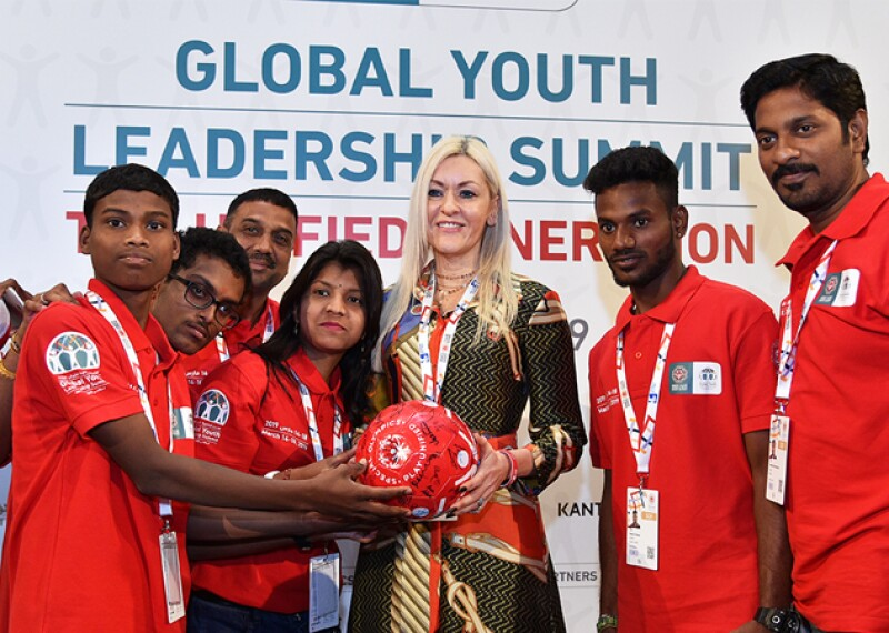 Six Special Olympics representatives comprised of youth leaders and adults stand on either side of a female Kantar representative with long blond hair.