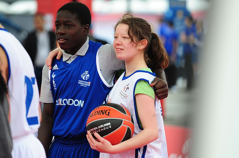 Boy and girl on the court with their arms around one another looking off into the distance. Girl is holding the basketball with a white take top and green short sleeve shirt under. The boy has on blue shorts and a take top with a gray collared athletic short sleeve shirt under.