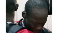 Mame Ndiagne Ndiaye being embraced by his team mates after hearing for the first time. He has hearing aids in each ear.