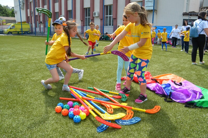 Children in yellow t-shirts holding colourful plastic hockey sticks with other colourful equipment and balls laid out on the grass beside them.