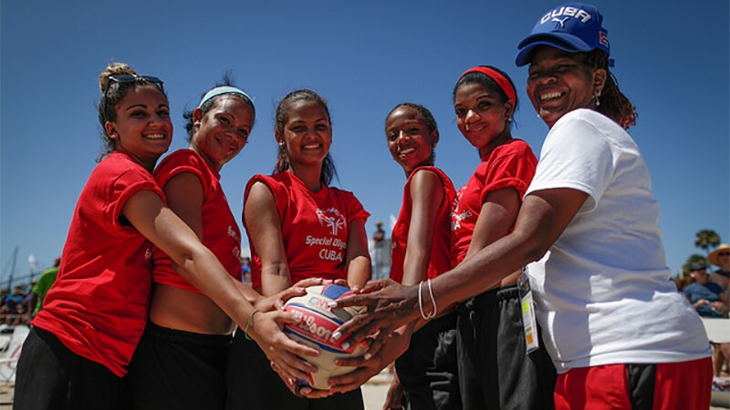 A woman's volleyball team all holding the ball for a group picture.