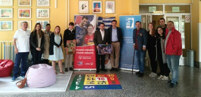 A group of people pose for the camera, standing between Special Olympics branding in a school.