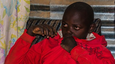 Zadock Mavinda, a 16-year old, sits in his house during the Golisano Foundation's visit.