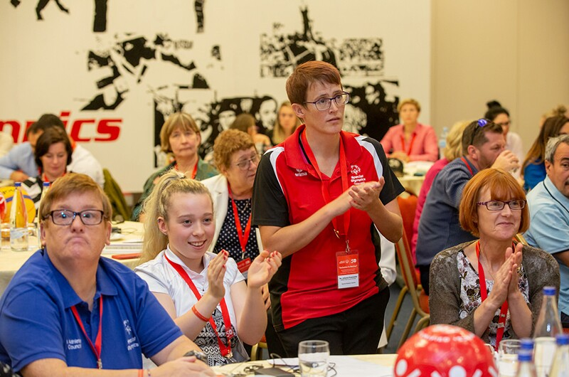 Athlete leaders Micheline Van Hees, Kiera Byland and Johanna Pramstaller with Jacqui Byland at the Special Olympics Europe Eurasia Leadership Conference 2018. One athlete is standing and speaking in the crowd and listeners are applauding.