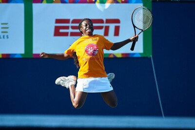 Female tennis athlete jumping up in the air for joy. She's holding her racquet in her left hand, has a white tennis skirt and a yellow Special Olympics t-shirt.