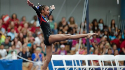 Young girl performing a artistic gymnastics routine.