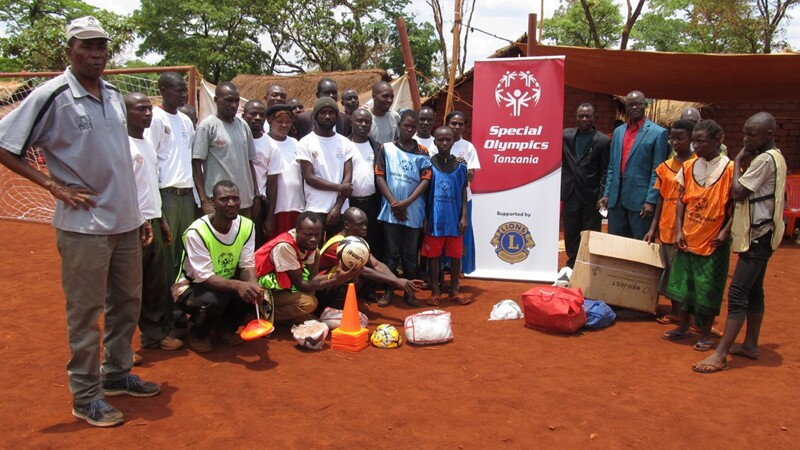 Group of people in 2 rows standing and one row crouching, outside next to Special Olympics Tanzania Lions Clubs signage.